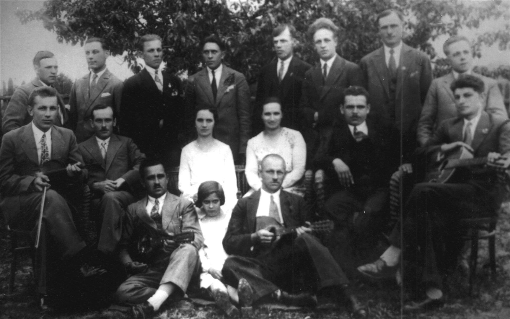 Józef Twaróg ze swym ulubionym instrumentem - skrzypcami (siedzi na krześle pierwszy z lewej) wraz z członkami zespołu muzycznego. W centrum na trawie siedzi ówczesny kierownik szkoły w Księżomierzu - Julian Mazepa. Księżomierz I połowa lat 30-tych XX wieku.