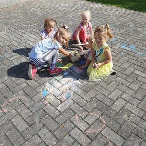 Dzieci rysują kredą, różnej wielkości kółka na kostce brukowej