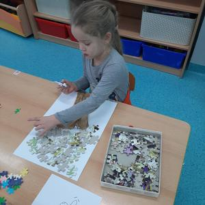 Dziecko z grupy Krasnale wykonuje drzewo z puzzli
