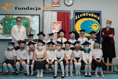 Uczniowie klasy pierwszej wraz z wychowawcą i Dyrektorem ZSP w dniu pasowania na ucznia. W tle nowy monitor interaktywny, zakupiony z darowizny Fundacji JSW, obok flaga Polski z godłem oraz logo ZSP Golasowice